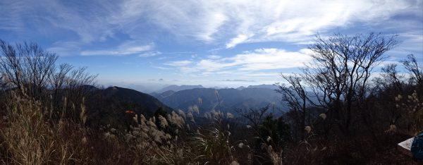犬ヶ岳直下のベンチで見るパノラマ。遠方に由布岳や九重山群、小枝の中に阿蘇山まで見える。