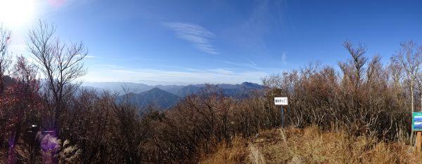 一ノ岳山頂のパノラマ。白い看板の左先に見る山が英彦山。